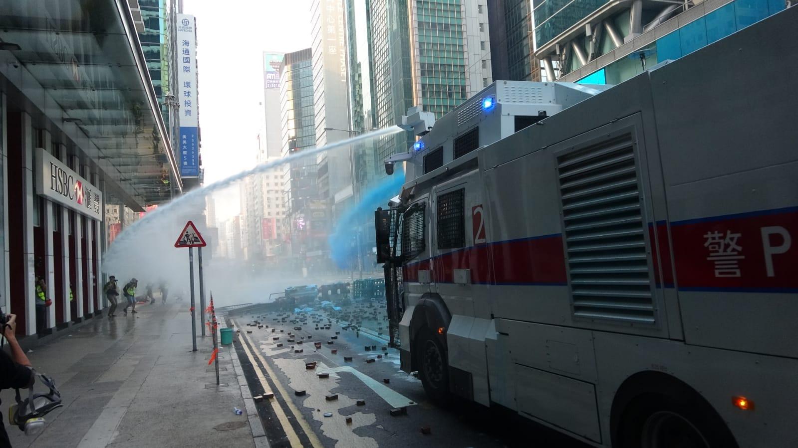 水炮車射藍水驅散。