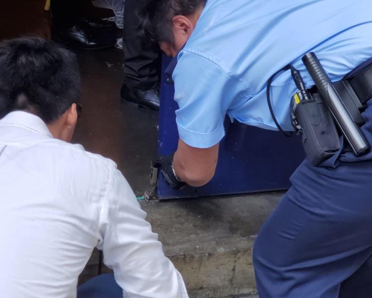警員檢查被被撬毀的門鎖。楊偉亨攝