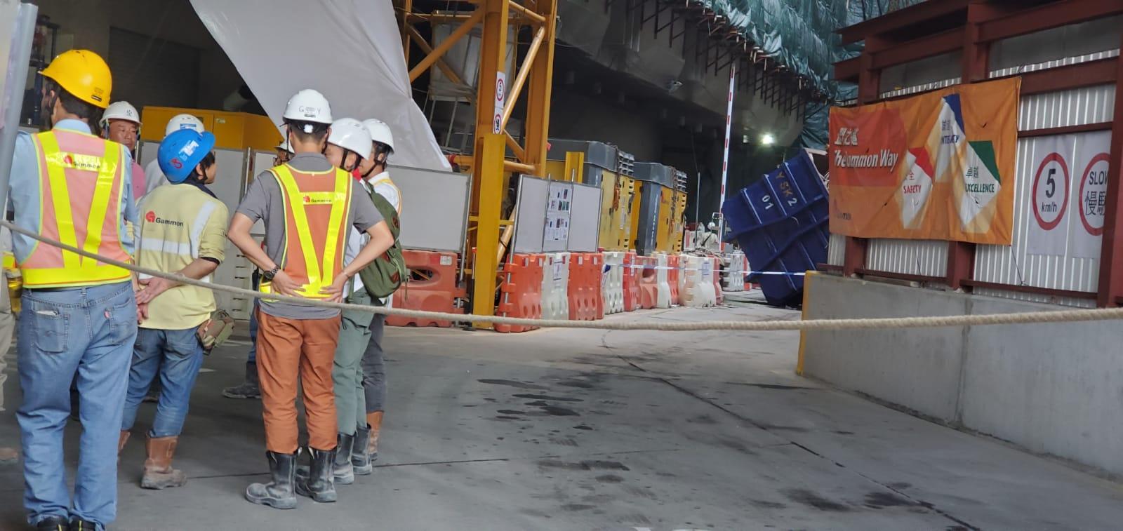 地盤內一個垃圾斗突然翻側,一名工人走避不及被壓中。 楊偉亨攝