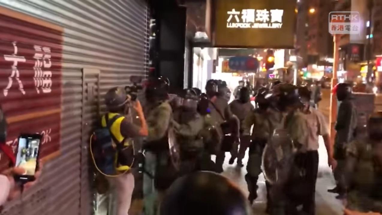 香港電台一名攝影師昨晚在旺角採訪期間,被警員扯下面罩。港台截圖