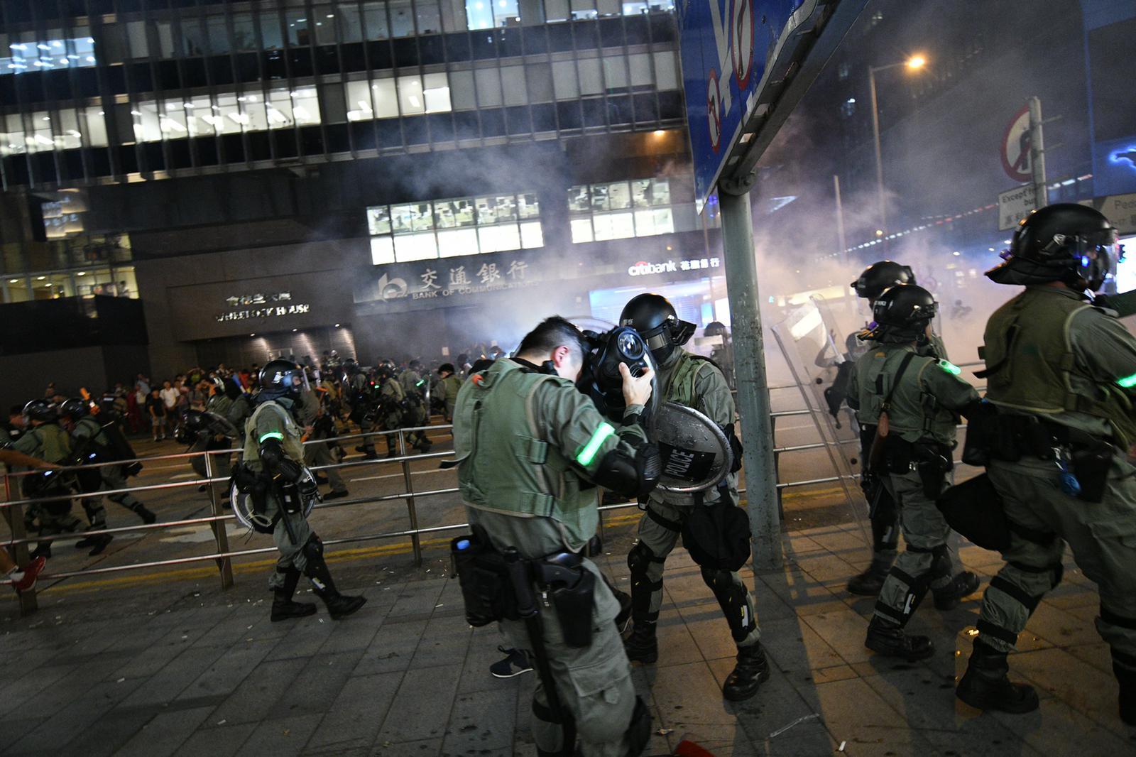 防暴警察未及佩戴防毒面罩。