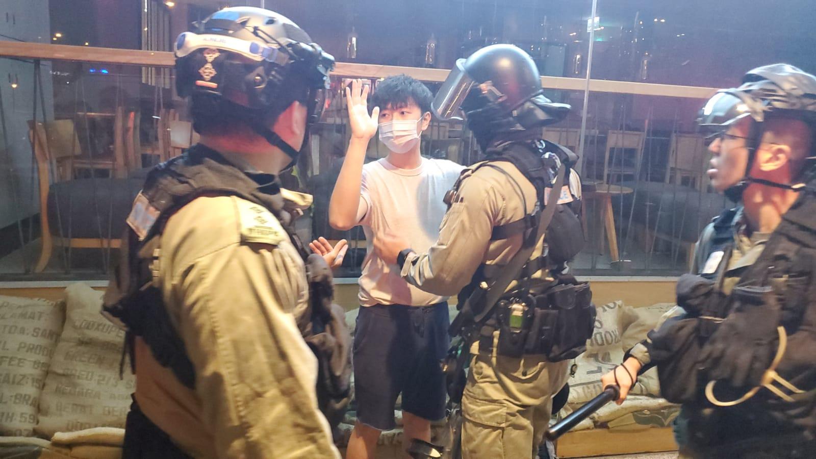 一名戴口罩男子被警員調查。