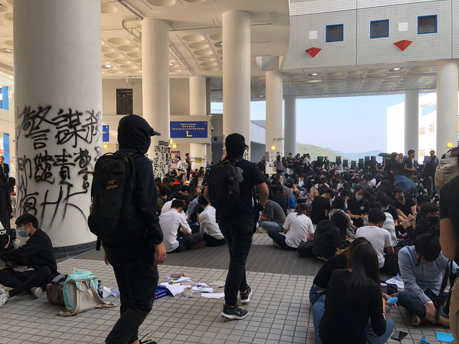破壞行動結束後,學生們撐傘經吳家瑋學術廊走回賽馬會大堂坐下。