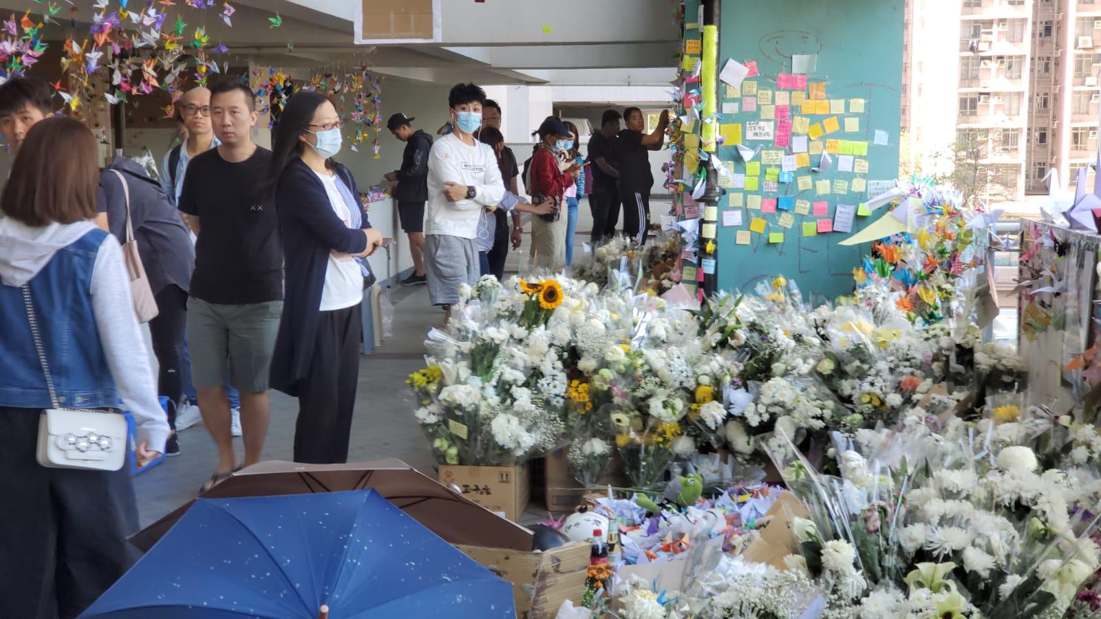 墮樓現場有大量由致祭人士放下的白花和寓意祝福的紙鶴。