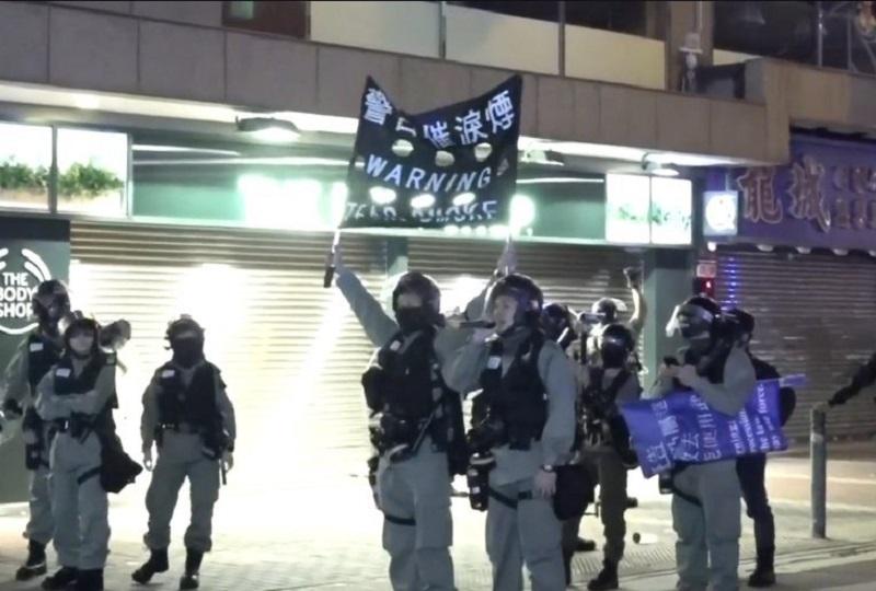 防暴警察展示黑旗。港台電視截圖