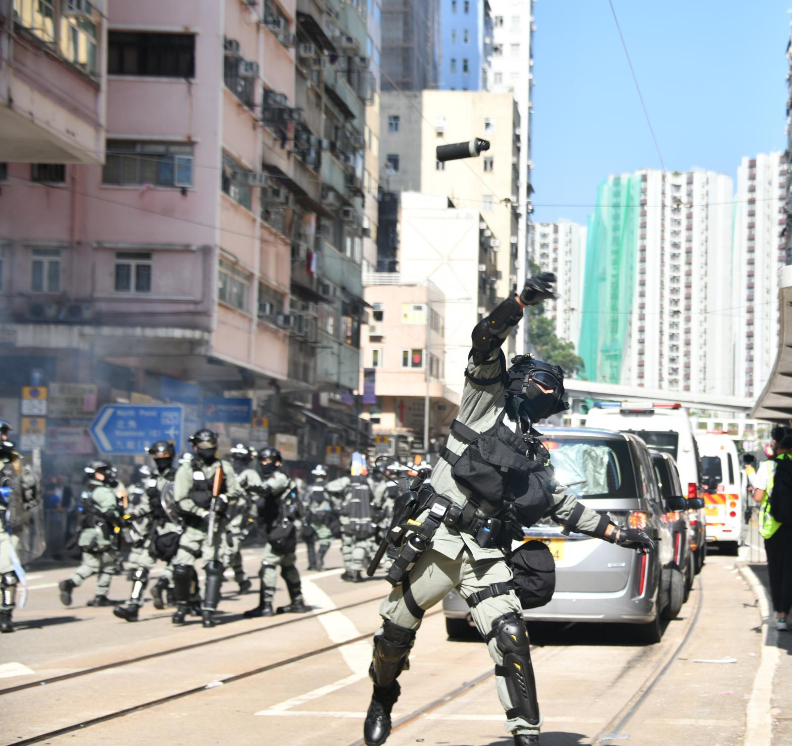 防暴警員衝出,在筲箕灣道舉黑旗和發射催淚彈。