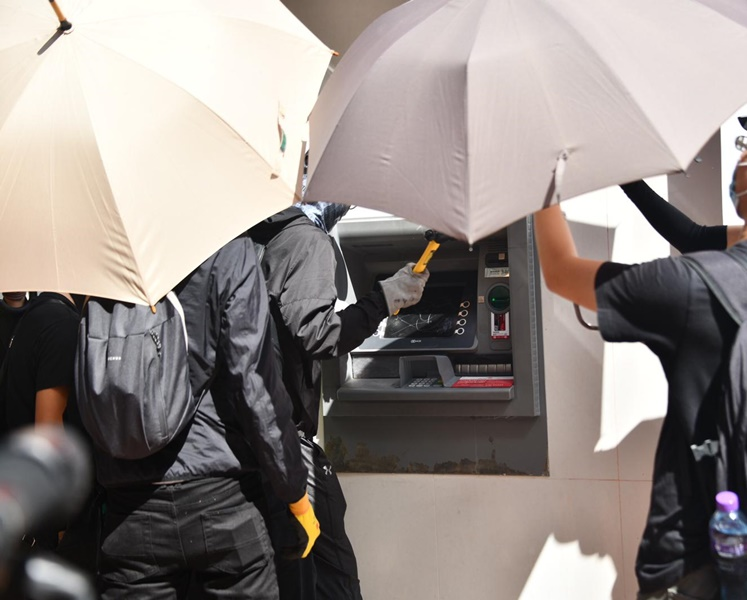 持硬物示威者在同行掩護下破壞自動櫃員機。