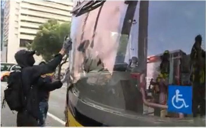 一輛機場巴士被噴漆塗鴉司機位擋風玻璃。NOW新聞截圖