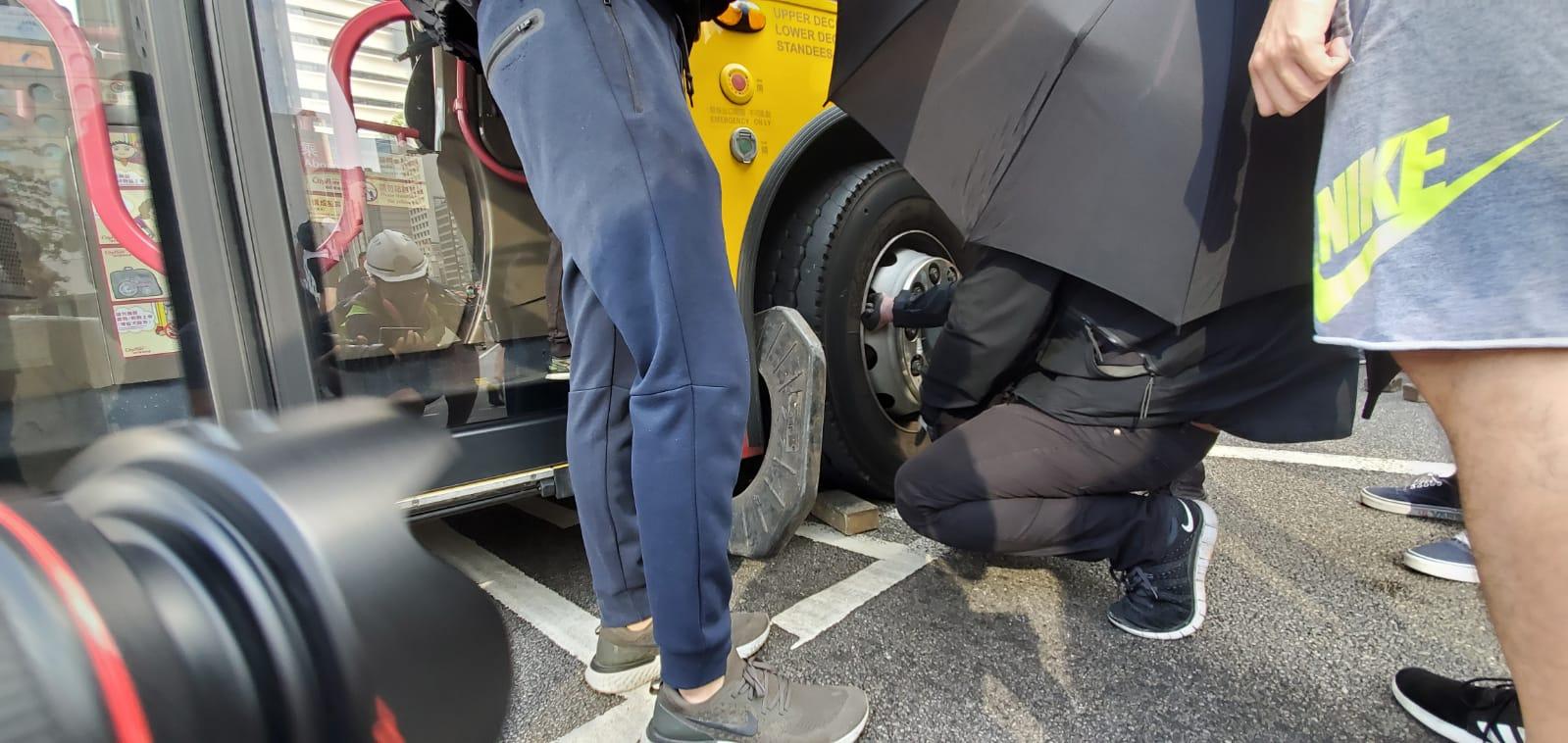 有示威者用磚頭卡住巴士車胎。