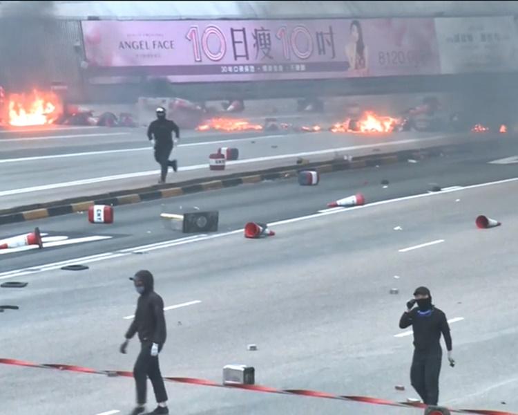 蒙面黑衣人在紅隧九龍出入口焚燒雜物。港台新聞截圖