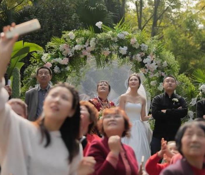 四川一對新人的婚禮上,有直升機在空中撒利是及鮮花,賓客看得目瞪口呆。(網圖)