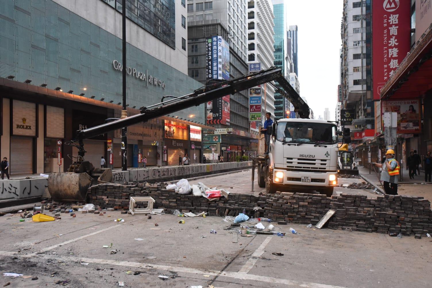 夾斗車清理馬路上堆砌的矮磚牆。