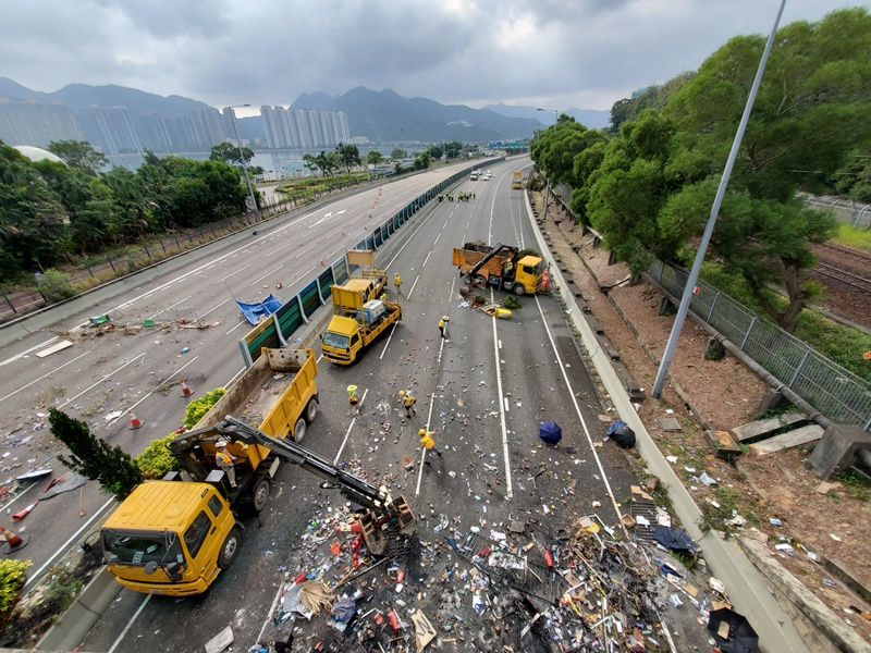 夾斗車清理吐露港公路堵塞的雜物和磚塊。