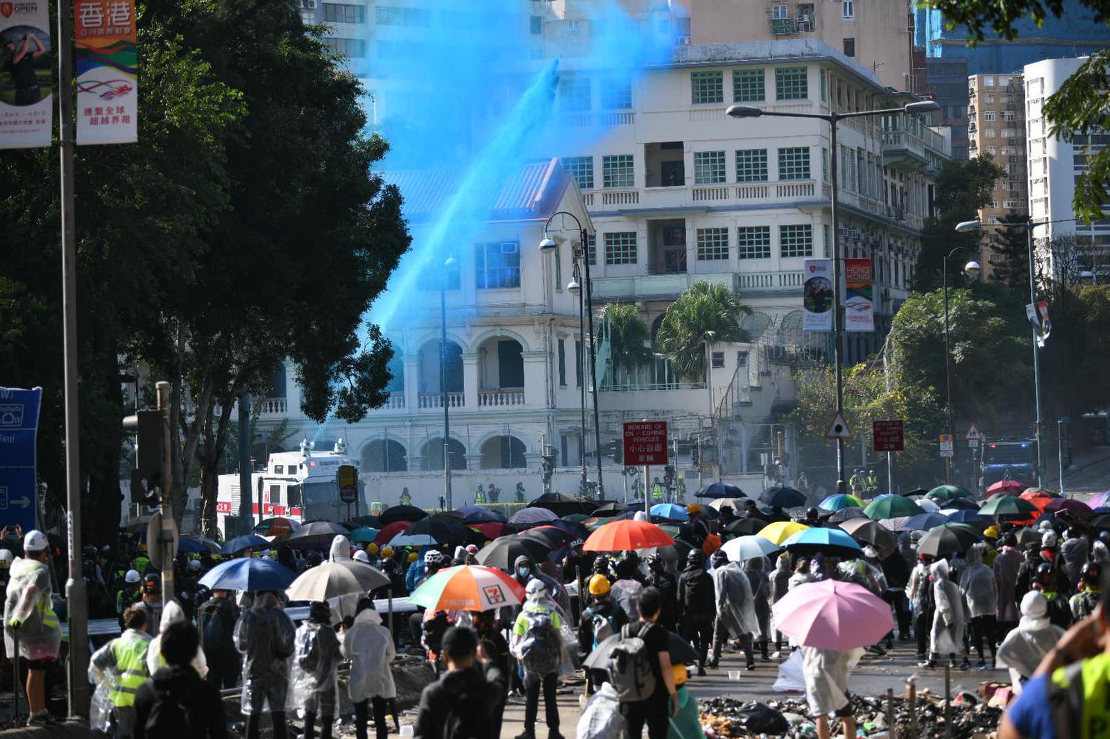 水炮車射出藍色水驅散。