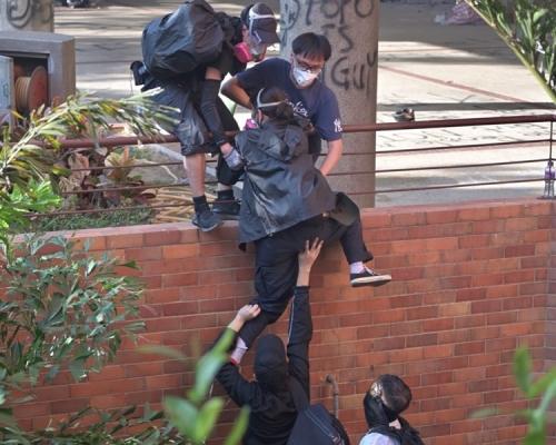 【修例風波】理大黑衣人圖集體離開遇催淚彈 有人爬欄折返