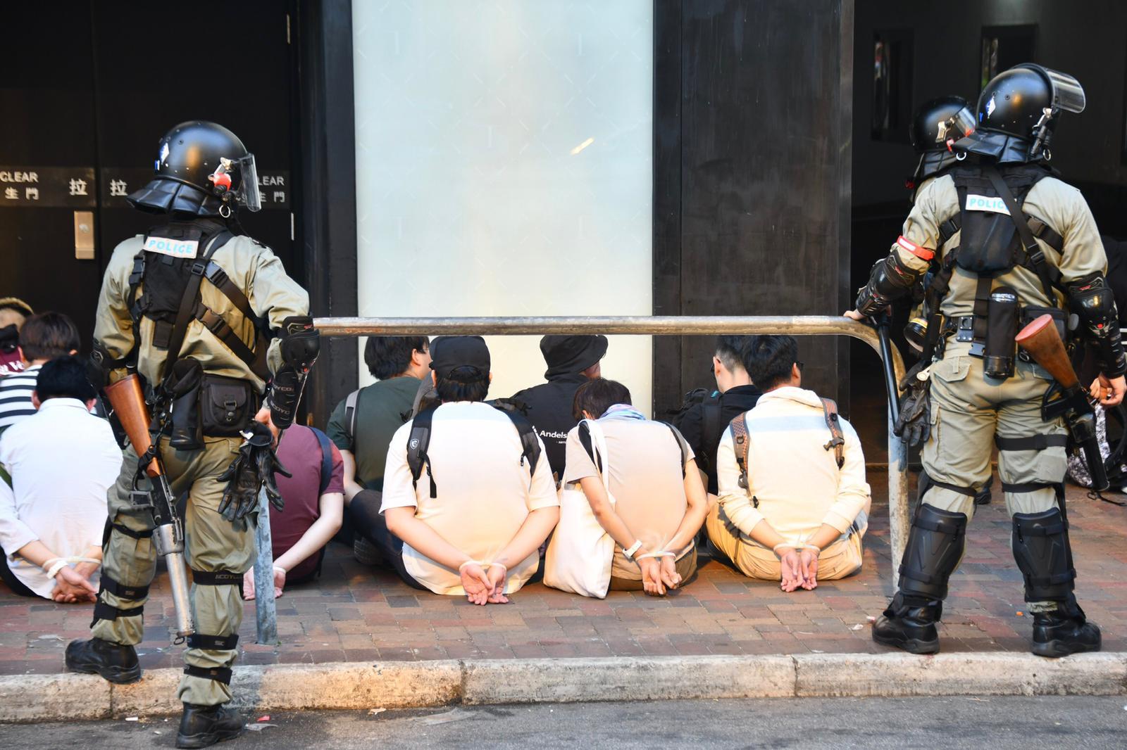 被截獲的人士全部雙手綁上索帶,背囊放前坐於地上。
