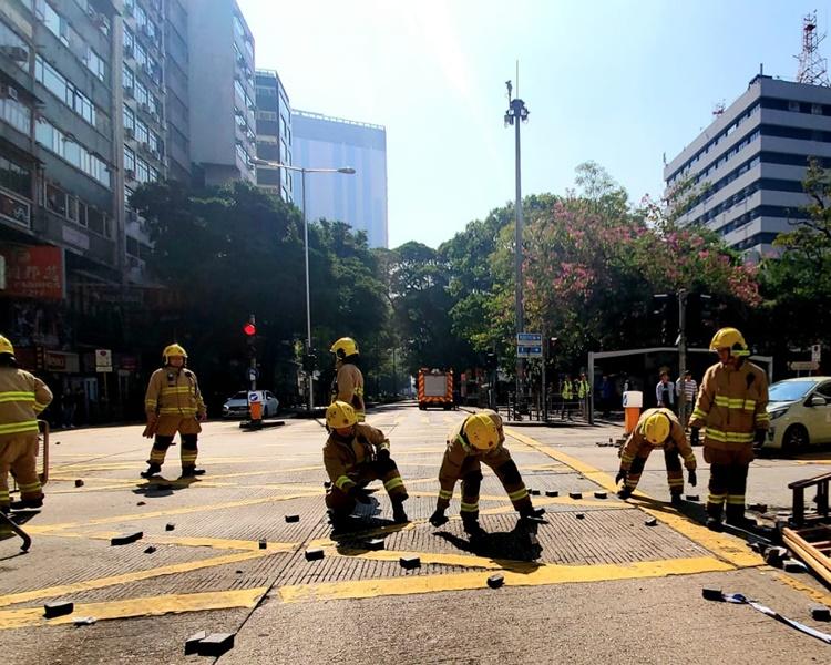 消防員幫手剷走馬路上的路障,搬走鐵欄及地磚。林思明攝