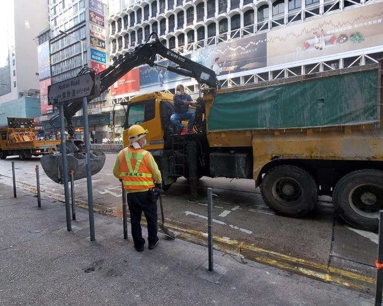 夾斗車將馬路上的大量磚塊夾起吊走。林思明攝