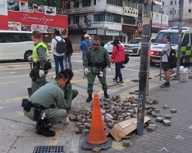 早警方及食環署清潔工人忙於清理馬路上的磚頭雜物。林思明攝