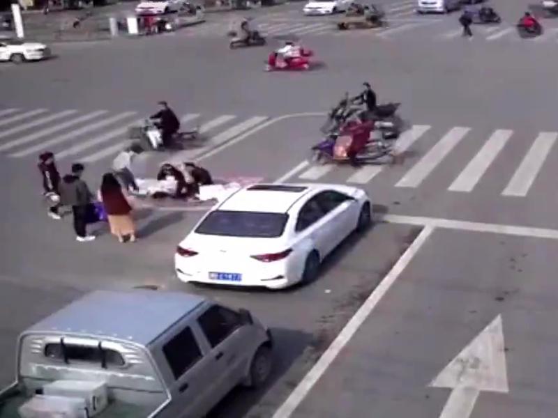 一對情侶竟躺在車水馬龍的大馬路上拍起婚妙照,他們旁若無人的大擺POSE,讓路過的人車都看得目瞪口呆。(網圖)