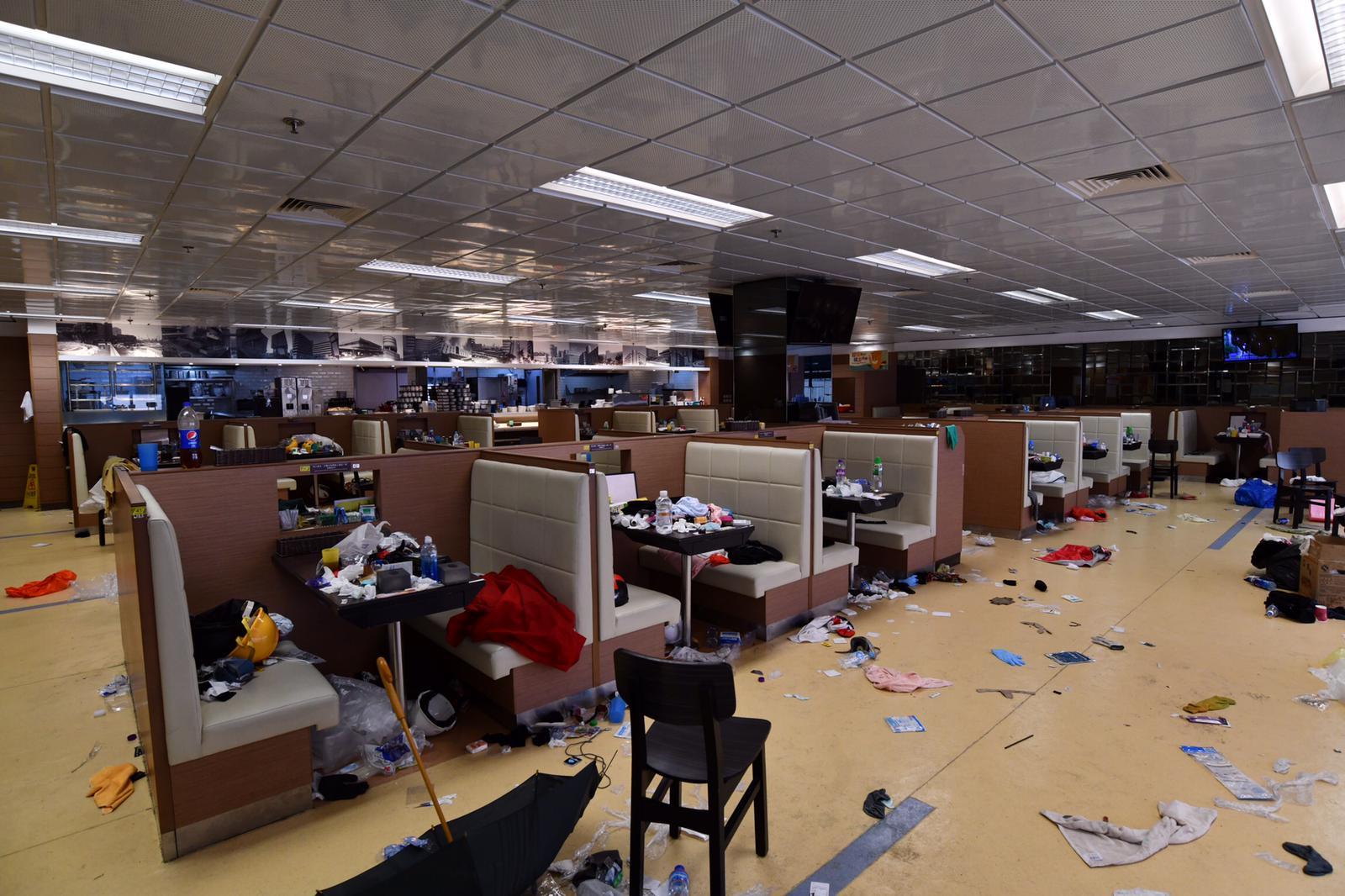 飯堂的桌椅和地上滿是膠水樽、頭盔與雜物,凌亂不堪。