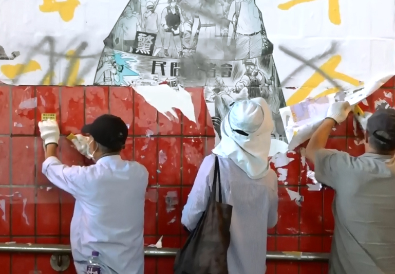 工人清理大埔連儂牆 。 香港電台視像新聞截圖