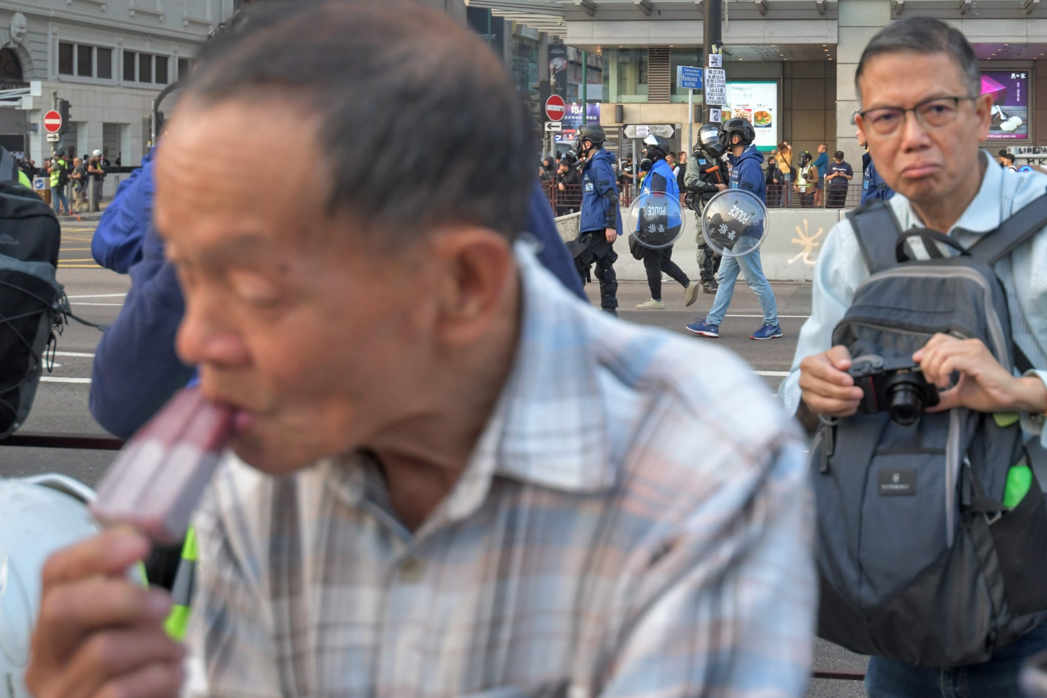 年近八旬的雪糕小販歐陽先生(前)中催淚彈後繼續擺檔