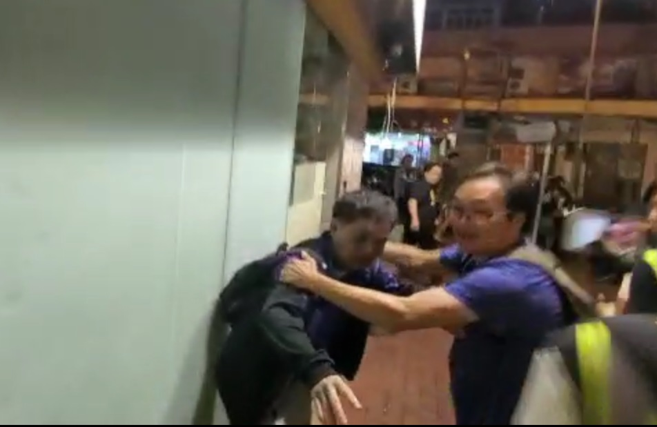 一名男子阻止示威者繼續襲擊男女。影片截圖