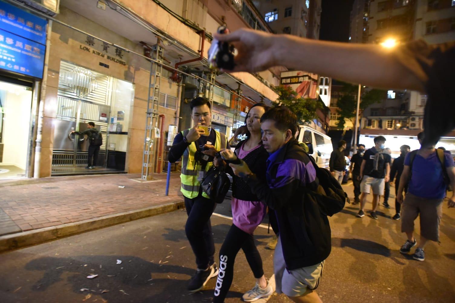 男女遭示威者包圍後離開現場。