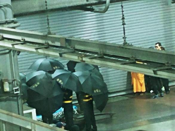 在法師引路下,工作人員以黑傘護送靈柩上靈車。