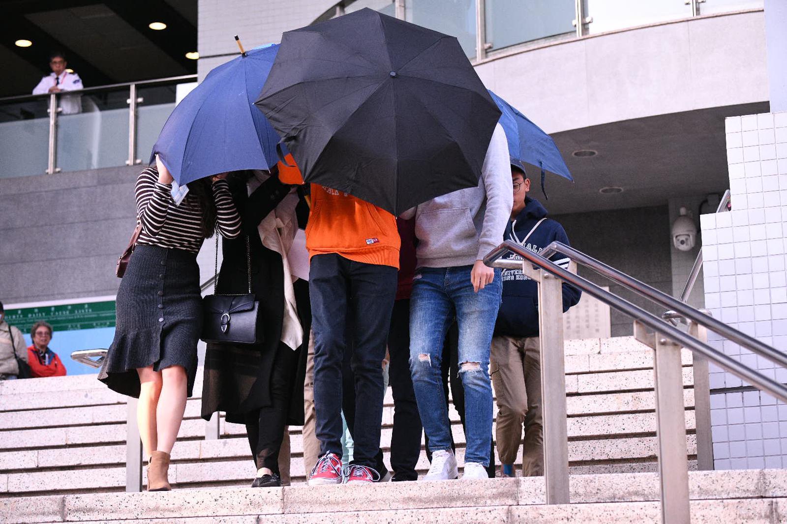 被告離開法庭時被傘陣包圍。