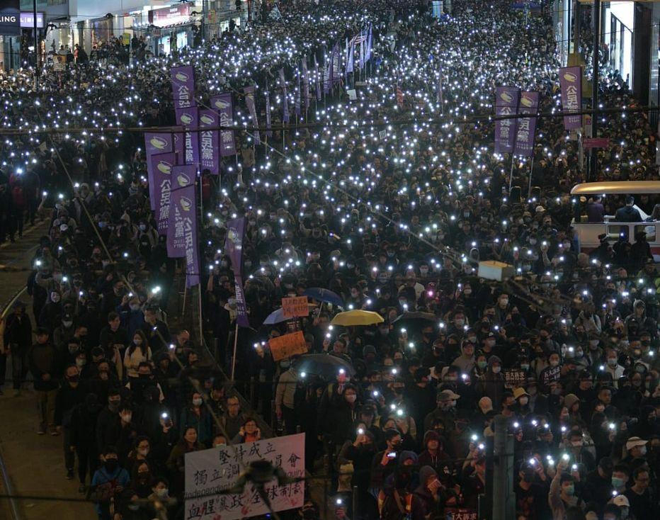 有遊行人士亮起手機燈。