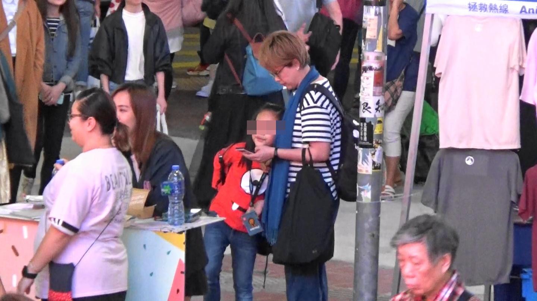 劉曉彤在銅鑼灣街頭顧住撳手機,在旁的囡囡就不停挨住對方,嗲吓媽咪。