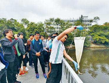 公大科技學院教職員帶同學生到城門河考察,向學生展示以專業儀器抽取水樣本。