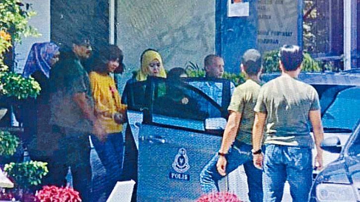 第二名女疑犯周四下午被押解離開雪邦警局,她身穿黃色衣服,戴着手銬。