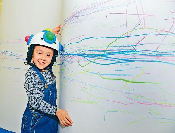 戴上五色彩蠟頭盔用頭在牆壁上繪畫,連後腦也有蠟筆球。