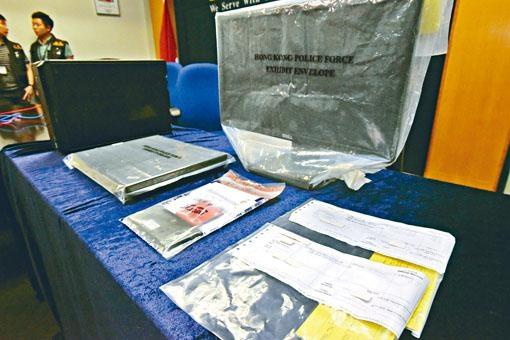警方展示涉案電腦與電話帳單等證物。