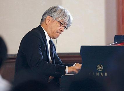 坐在鋼琴前彈奏的姿態充滿魅力。