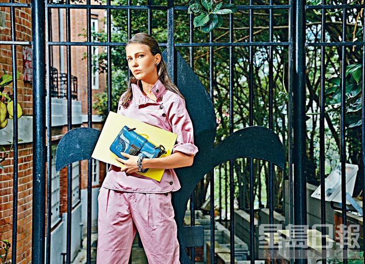 粉紅色棉混絲上衣、粉紅色棉混絲長褲、藍色漆面水蛇皮Darling手袋。
