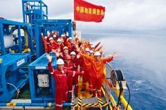 參加試採的中國科研及施工人員在鑽井台上慶祝試採成功。