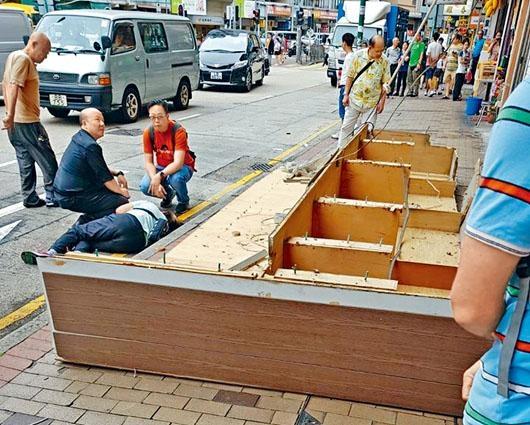 五米長木製巨型招牌塌下,女途人被壓中傷臥路邊,可見招牌露出膠塞螺絲。