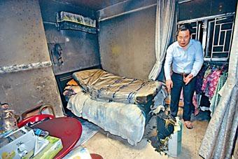 戶主指着起火的抽濕機,可見牀褥及房間熏黑。
