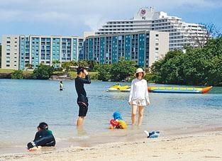 遊客在關島首府阿加尼亞的海灘遊玩。