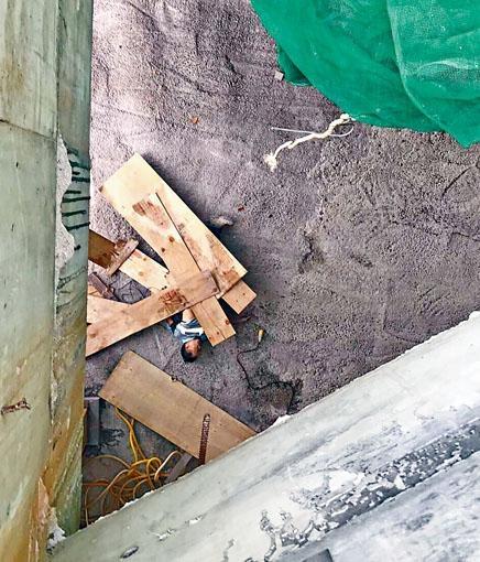 燒焊工人嚴潤恩連木板墮地慘死,身體仍被部分木板壓着。