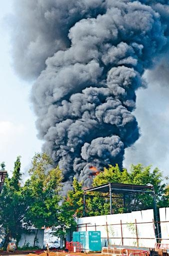 堆積回收物料的火場不斷冒出有毒黑煙。