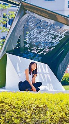 連日天晴酷熱,一名市民利用藝術品遮擋陽光乘涼。