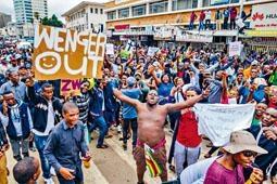 有津巴布韦国民在反总统示威中高举「云加out」的横额。