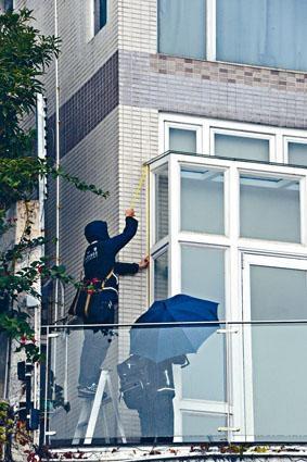 屋宇署人員在律政司司長鄭若驊海詩別墅大宅量度外牆違建物。