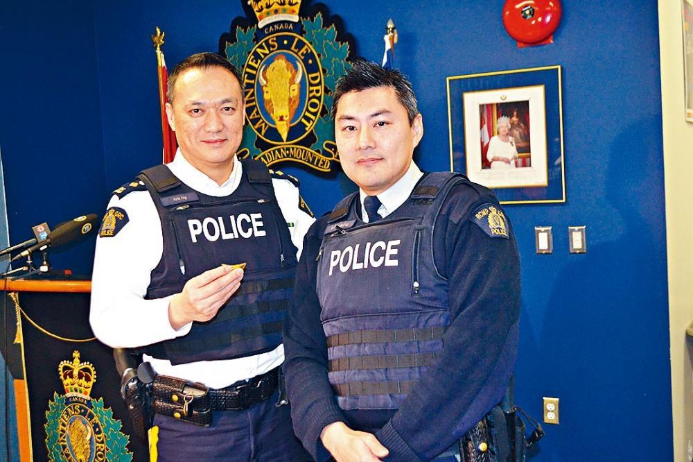 列治文警隊「一哥」吳潤明(左)拿著懷疑假金元寶,與梁比利合照。馮瑞熊攝