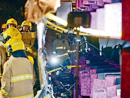 ■消防員在毀爛不堪的巴士車廂內搜索。